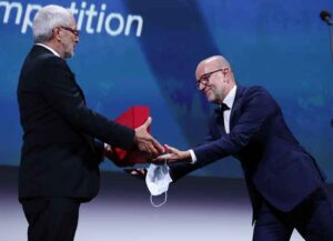 """VENICE, ITALY - SEPTEMBER 12: Davide Romani (R) receives the Golden Lion for Best Film on behalf of US director Chloe Zhao for """"Nomadland"""" from President of the Venice Biennale Roberto Cicutto (L) during the closing ceremony at the 77th Venice Film Festival on September 12, 2020 in Venice, Italy."""