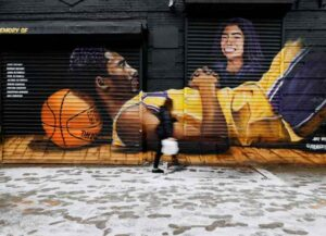 NEW YORK, NEW YORK - JANUARY 26: People walk by a mural memorializing Kobe Bryant and his daughter Gianna across from the Barclays Center on the first anniversary of their death on January 26, 2021 in the Brooklyn borough of New York City. The mural was painted last year by Efren Andaluz III, better known as Andaluz The Artist. (Photo by Sarah Stier/Getty Images)
