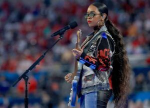"""TAMPA, FLORIDA - FEBRUARY 07: H.E.R. performs """"America The Beautiful"""" before Super Bowl LV between the Tampa Bay Buccaneers and the Kansas City Chiefs at Raymond James Stadium on February 07, 2021 in Tampa, Florida. (Photo by Mike Ehrmann/Getty Images)"""