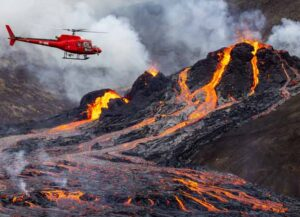 FAGRADALSFJALL, ICELAND - MARCH 20: (ICELAND OUT, no archiving and no use after 26th March 2021) A helicopter flies close to a volcanic eruption which has begun in Fagradalsfjall near the capital Reykjavik on March 20, 2021 in Fagradalsfjall, Iceland. On Friday the Icelandic meteorological office announced a volcano, referring to a mountain located south-west of the Capital Reykjavik has erupted after thousands of small earthquakes in the area over the recent weeks. A no-fly zone has been established in the area. (Photo by Vilhelm Gunnarsson/Getty Images)