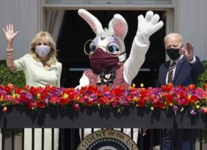 U.S. President Joe Biden, right, and First Lady Jill Biden wave beside a costumed Easter bunny from the Truman Balcony of the White House in Washington, D.C., U.S., on Monday, April 5, 2021. The Biden administration is aiming to corral overwhelming public support for its $2.25 trillion infrastructure plan, targeting Republican voters, independents, mayors, governors and local politicians to counter opposition from GOP lawmakers. Photographer: Michael Reynolds/EPA/Bloomberg via Getty Images